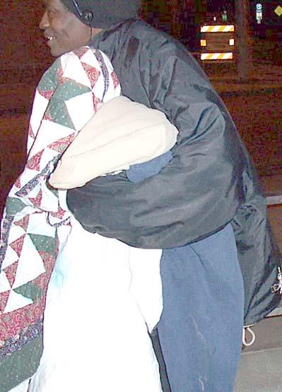 Homeless man holding blankets