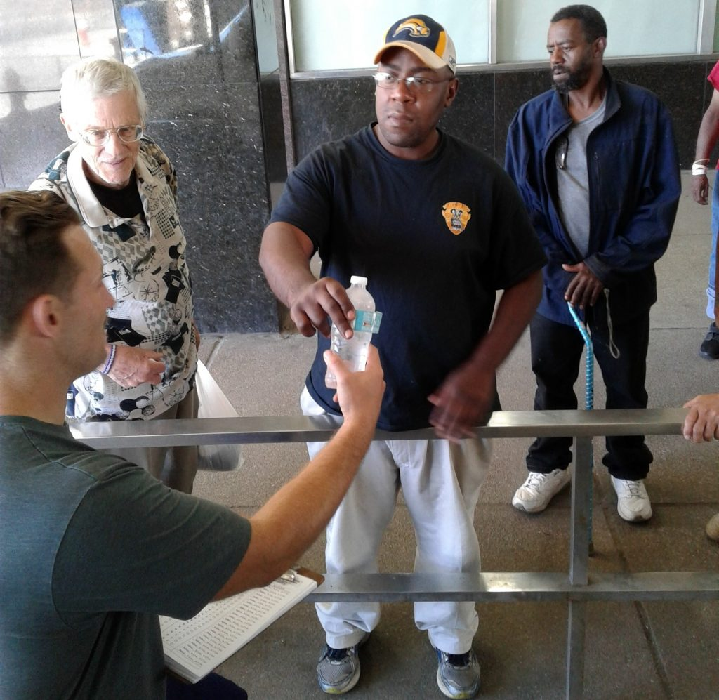 Homeless man receiving water bottle