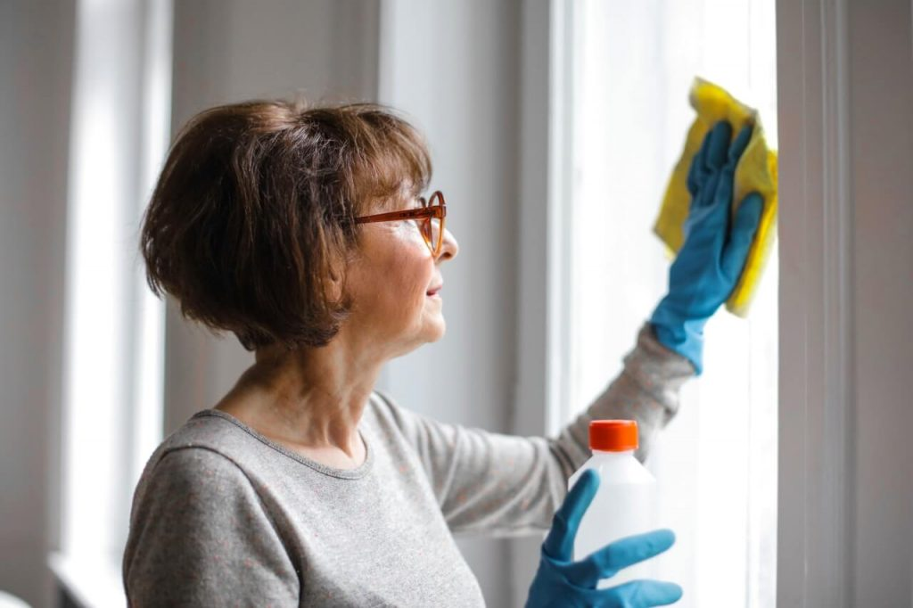 woman cleaning her windows wearing rubber gloves using sponge