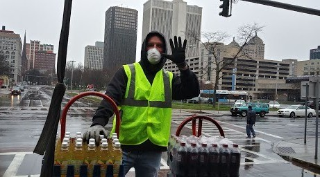 volunteer in green vest distributing drinks
