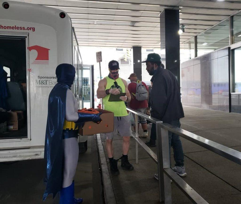 Man in Batman costume serving food to the homeless