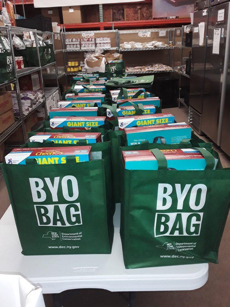 green eco bags filled with groceries awaiting distribution