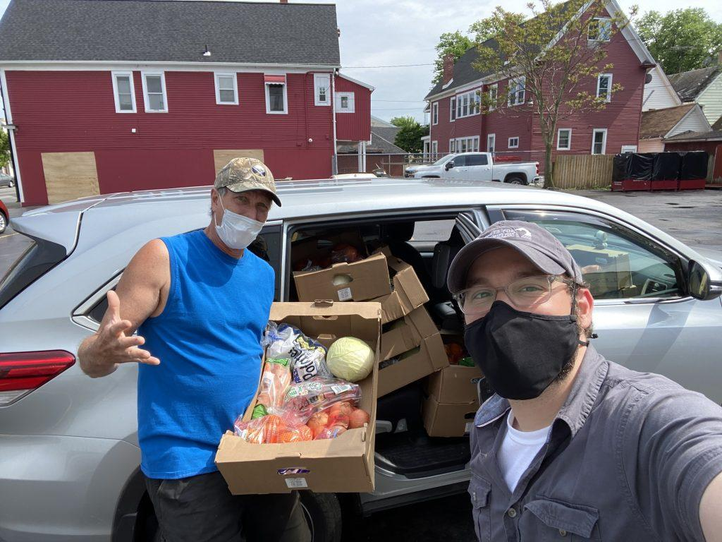 CEO Nick and Board Member Kevin stand in front of a car loaded with boxes of food