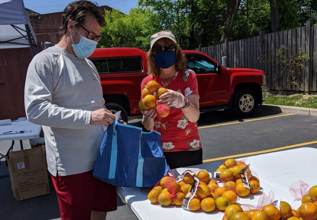 man and woman pack bags of oranges at a table outside