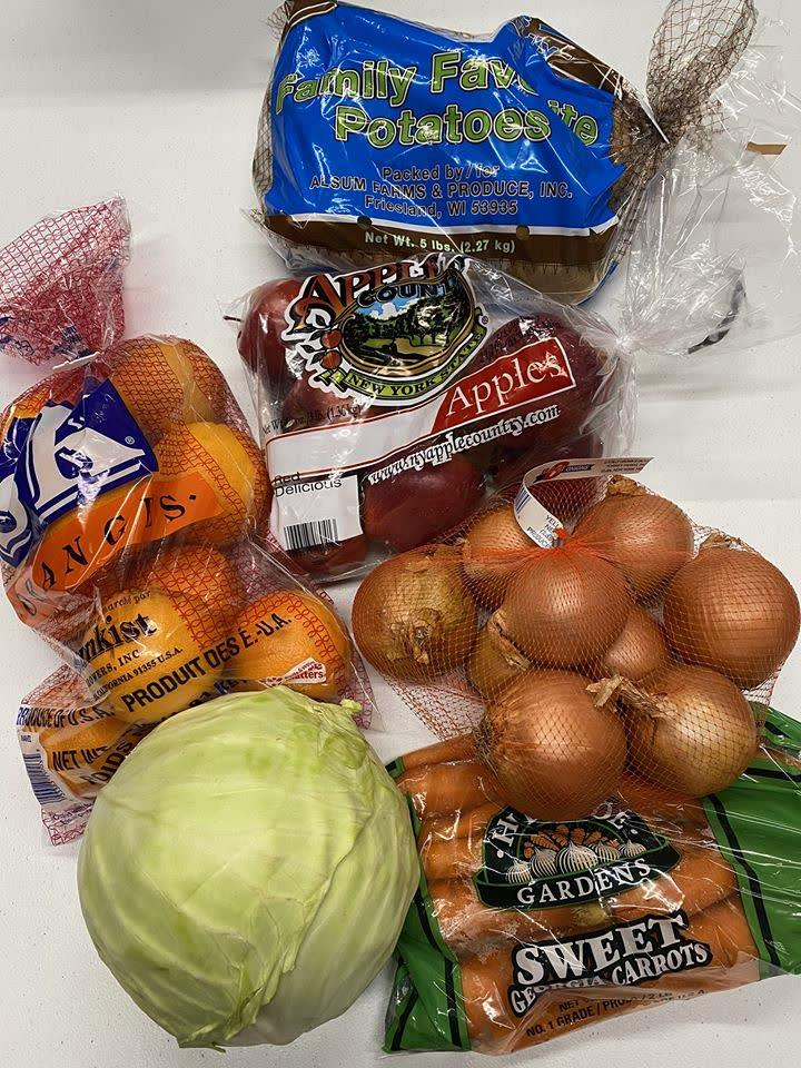 fresh produces in bags - cabbage, oranges, onions, carrots , apples and potatoes