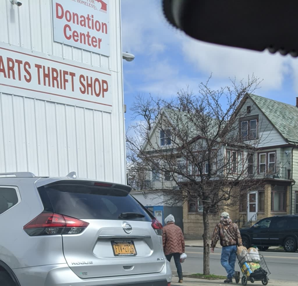 A local family walking with groceries received from our food pantry.
