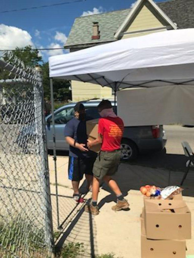 Hearts Mobile Food Pantry volunteer hands off food to a local family.