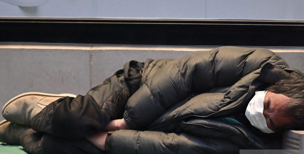 Homeless man lying down trying to stay warm