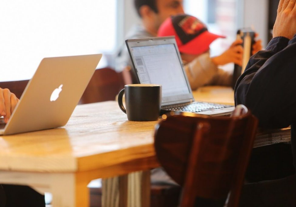 people sitting at a table in a cafe with laptops and coffee